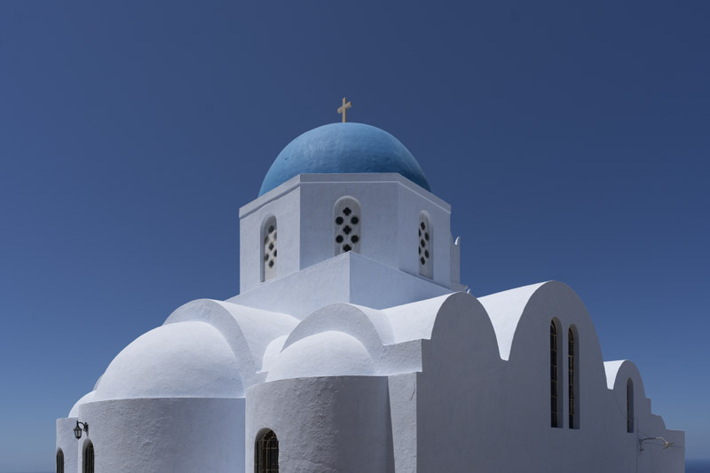 Blue domed church at Pyrgos under a bright blue sky