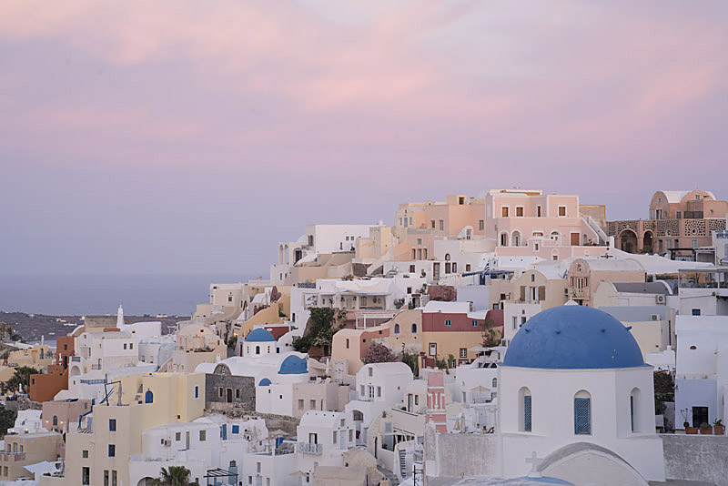 Colourful houses of Oia at dawn beneath a pink sky