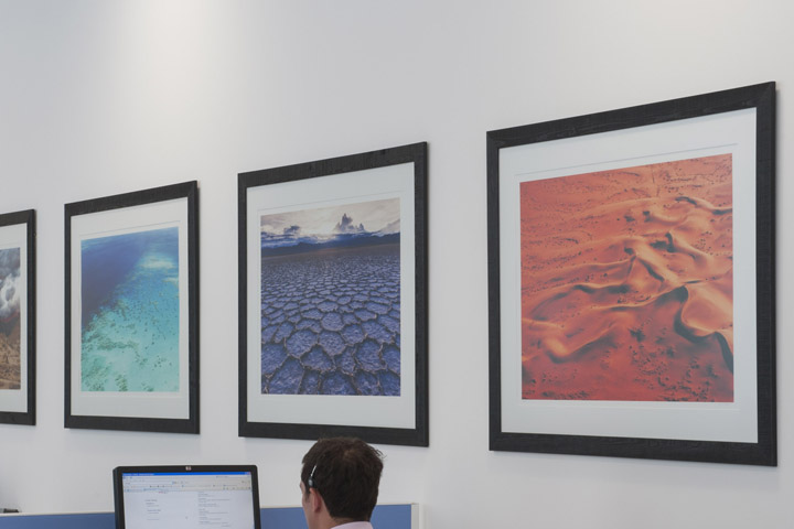 Framed photographs of the world in the offices of JD Haspel