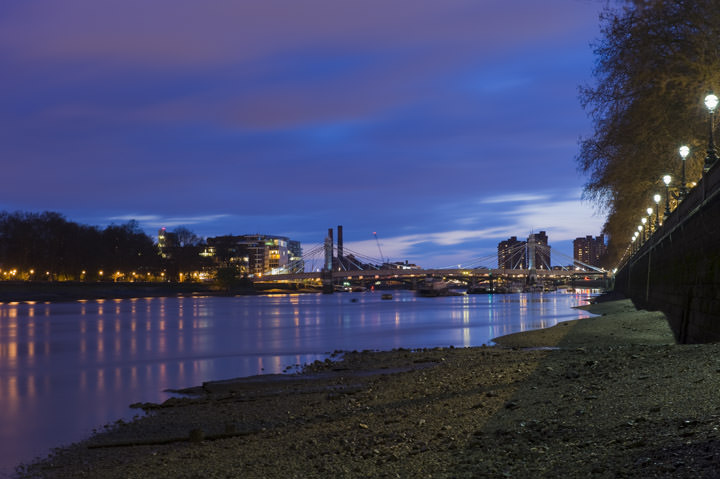 View of Albert Bridge and Battersea from banks of River Thames