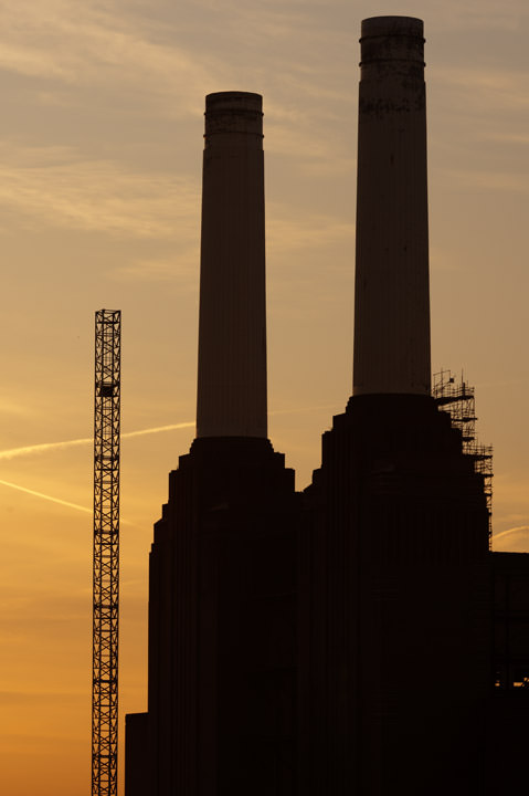 Two chimneys of Battersea Power Station at sunrise