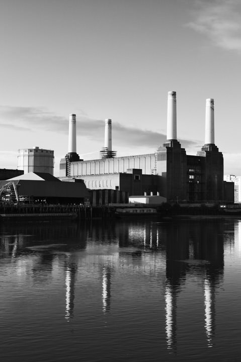 Black and white vertical photo of Battersea Power Station and reflection