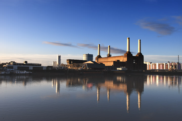 Dominant blue photo of Battersea Power Station and its reflection in the River Thames