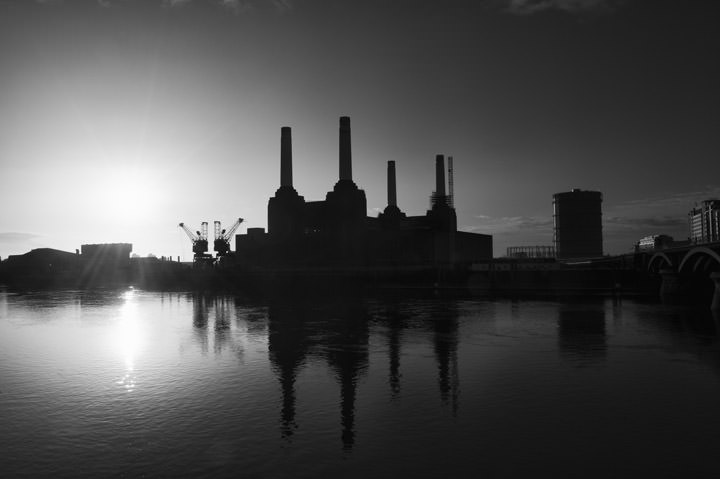 Sun rises behind Battersea Power Station in this black and white photo