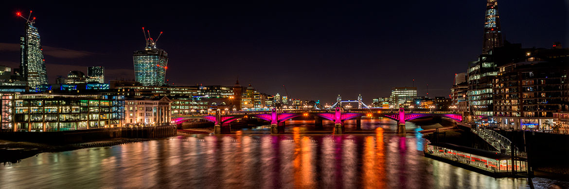 City of London skyline featuring Southwark Bridge lit in red at night