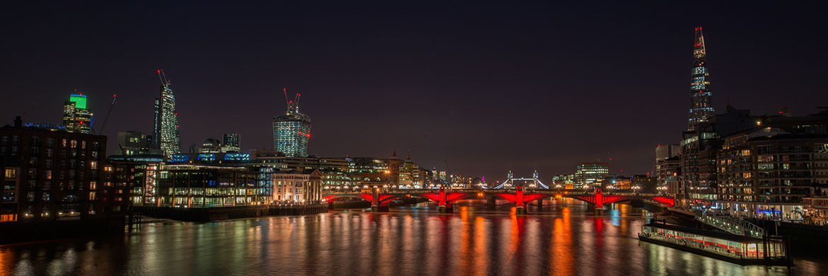 City of London skyline featuring Southwark Bridge lit in purple