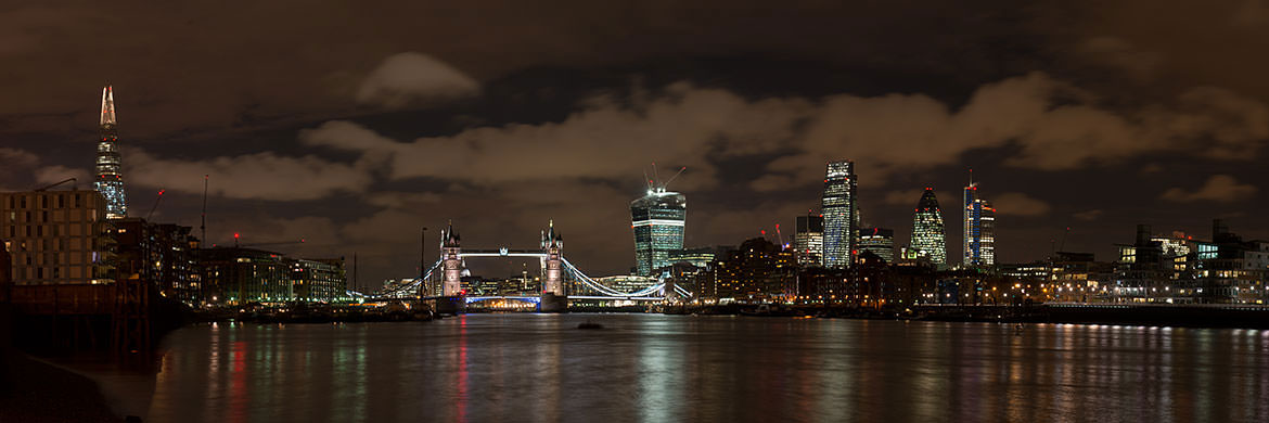 City of London panorama featuring  the recent additions to the City skyline beneath rain clouds at night.