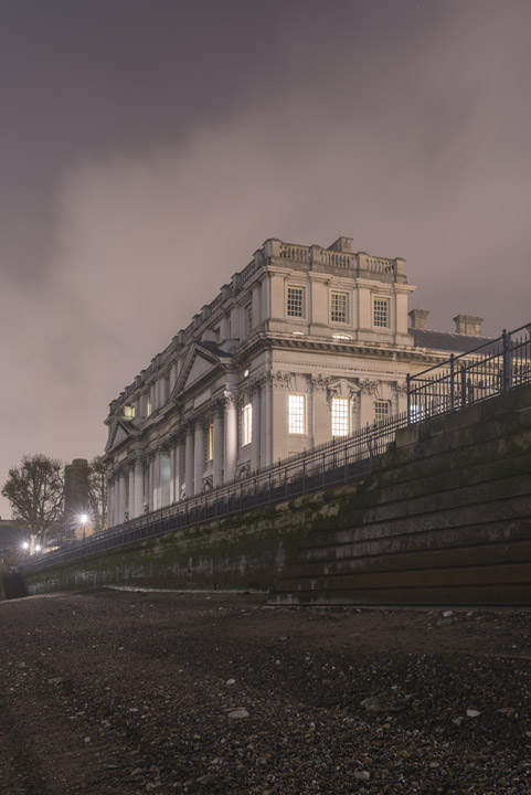 Vertical photo of Greenwich Naval College from the River Thames at night.
