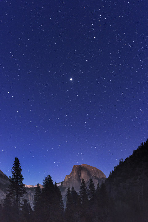Jupiter dominates a star studded sky over Yosemite at night.