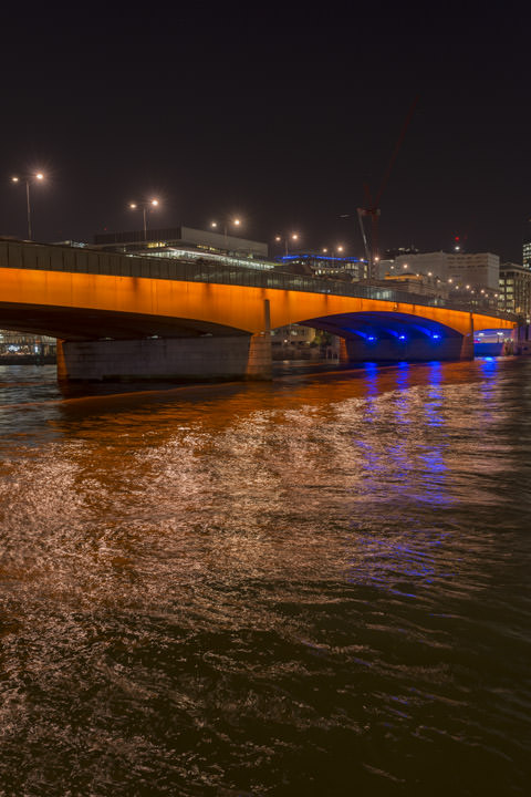 The lights of London Bridge reflected in the River Thames at night.