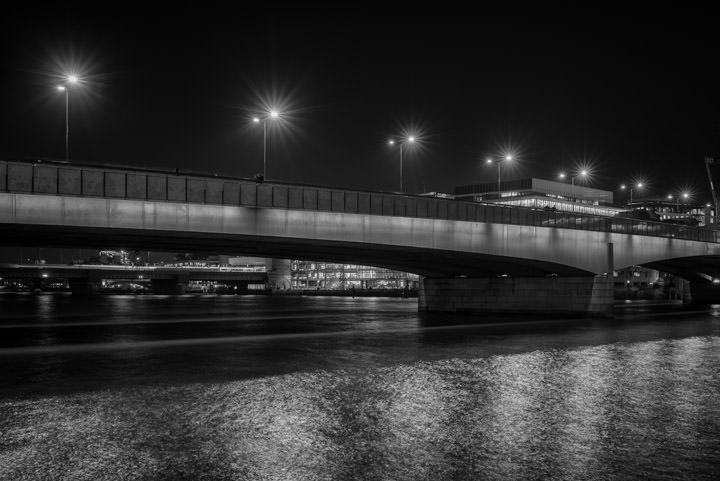Black and white photograph of London Bridge at night.