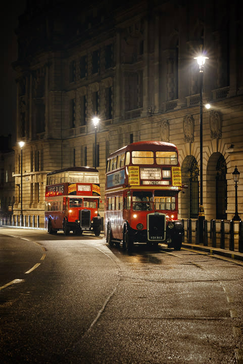 Two vintage buses on a wet night in London