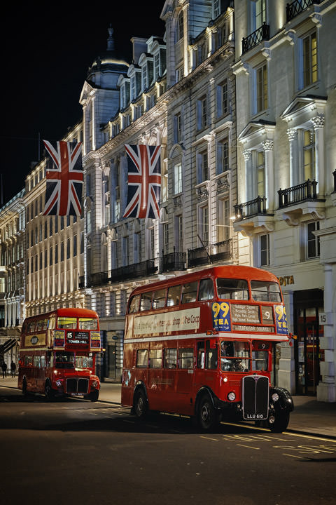 2 London Buses beneath Union Jacks