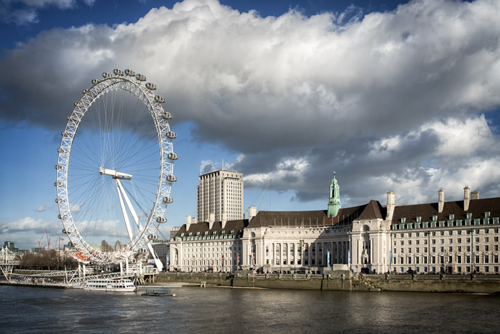 The London Eye beneath dramatic clouds in daytime