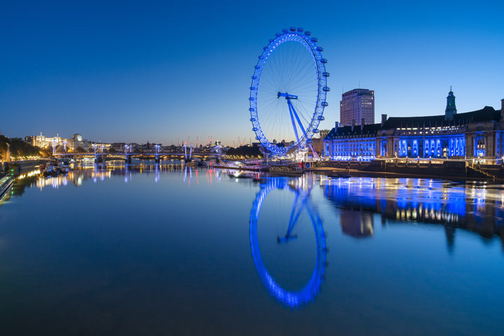 London Eye lit in blue at dawn with a deep blue sky and blue river thames