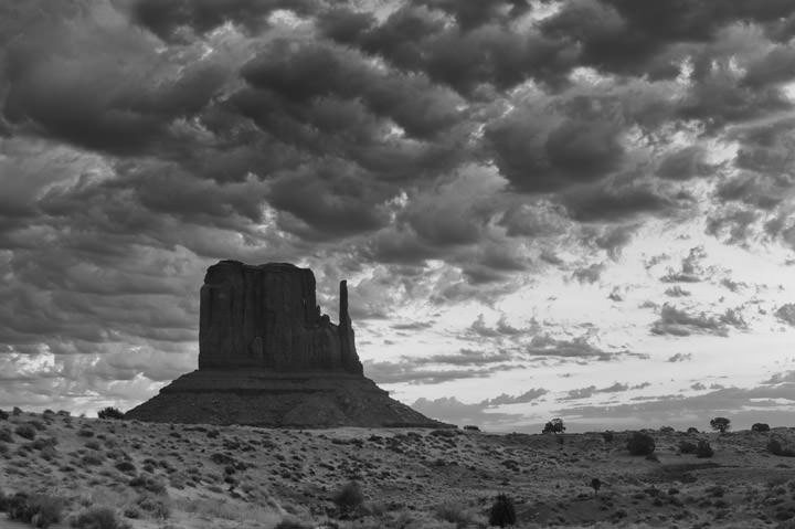 Monument Valley under a dramatic sky in black and white.