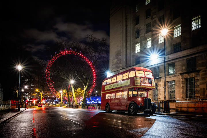 A Red Bus with the London Eye lit in red in the background at night