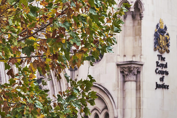 Royal Courts of Justice photographed in Autumn. Golden leaves and the signage of the Royal Courts of Justice.
