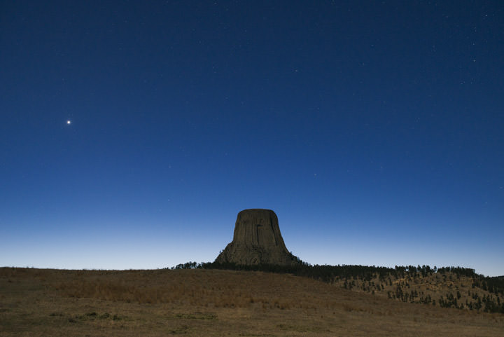 photograph of Devils Tower in Wyoming beneath a sky full of stars