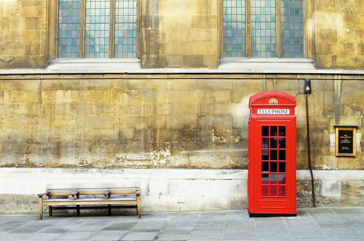 A red Telephone Box and bench outside a London church