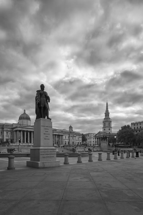 Black and white photograph of Trafalgar Square in the early morning.