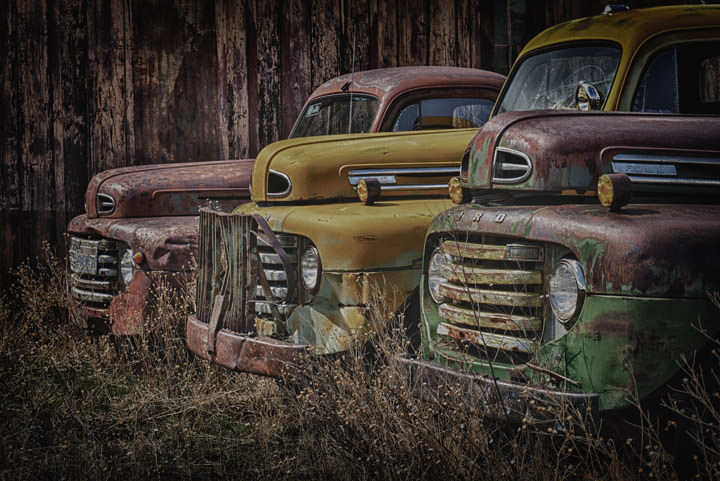 Three old farm trucks in colour