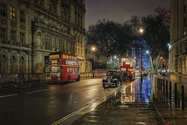 Two buses and a taxi on a wet night in London